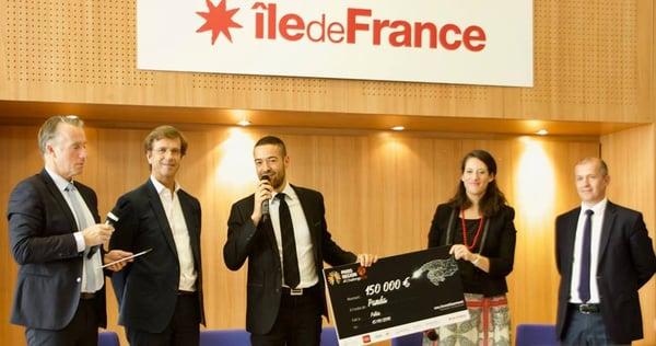 Photo d'Arnaud récupérant les 150 000 € de récompense sur scène