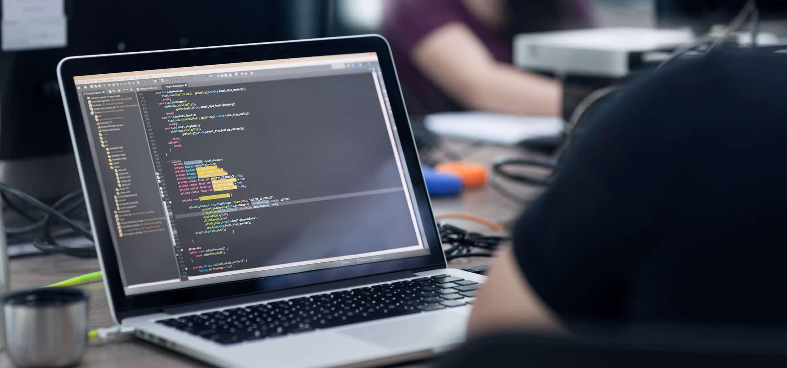 Photo d'un développeur web avec du code informatique sur l'écran de son ordinateur