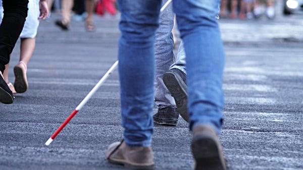 Photo d'une personne aveugle marchant dans la rue avec sa canne blanche