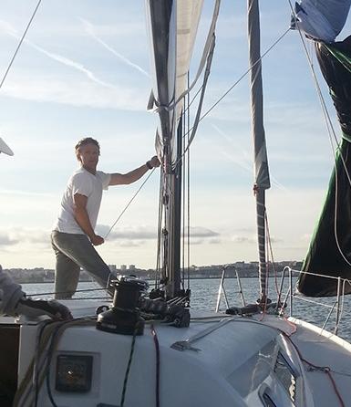 Photo de Mathieu sur son bateau hissant la voile