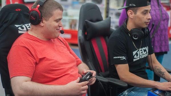 Photo de Sven, manette à la main, affrontant un joueur lors d'une compétition de e-sport