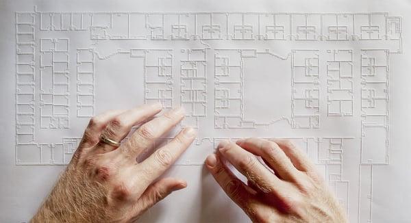 Photo du plan en relief d'un bâtiment avec 2 mains qui le parcourent pour le déchiffrer